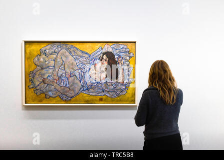 Schiele Vienna, rear view of a woman looking at a painting of a reclining woman (Liegende Frau) by Egon Schiele in the Leopold Museum, Vienna, Austria - Stock Image