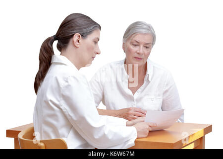 Female doctor showing her senior patient a paper bill or check, listing the costs of the medical treatment, isolated on white background - Stock Image