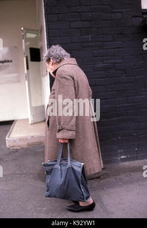 elderly woman walking alone on the street carrying a large hand bag - Stock Image