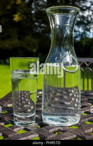 A one litre carafe and a glass on an exterior table in a garden - Stock Image