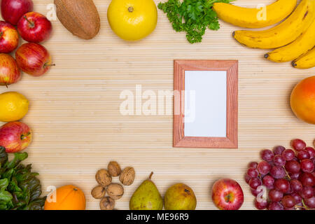 Flat lay of arranged wooden frame surrounded with plenty of healthy fresh fruit and gree on wood. - Stock Image