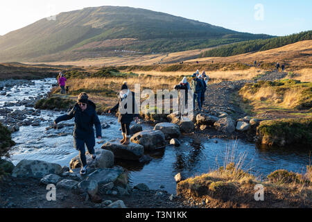 Tourists crossing the River Brittle on the way to the Fairy Pools, Isle of Skye, Highland Region, Scotland, UK - Stock Image