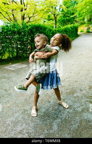 A young girl carries her little brother - Stock Image