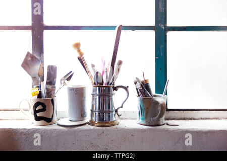 Paint brushes and tools in cup on window sill - Stock Image