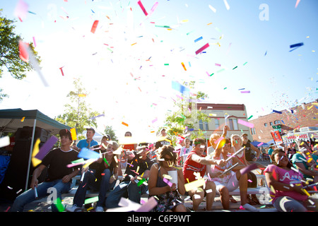 A group of people launch confetti into the air during a festival kick-off ceremony in Rogers, Arkansas. - Stock Image