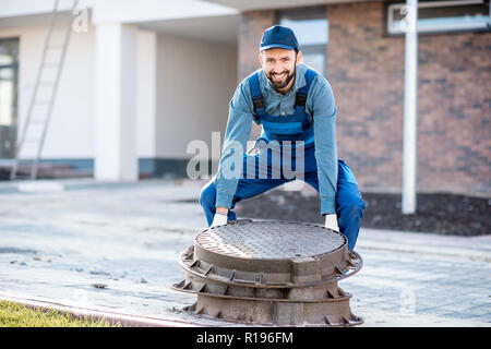 Workman in uniform mounting new road hatches at the residential area - Stock Image