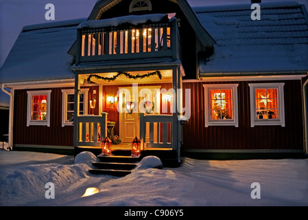 Christmas decorated Swedish house with front porch, at night - Stock Image