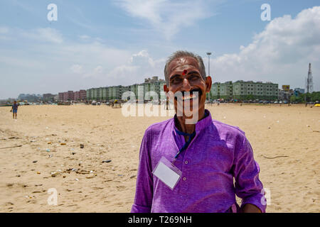 A moustached, smiling gentleman with a bindi enjoys the sea at Marina Beach, with the Bay of Bengal in Chennai, India - Stock Image