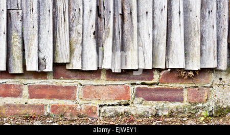 Weathered fence panels against a brick wall - Stock Image