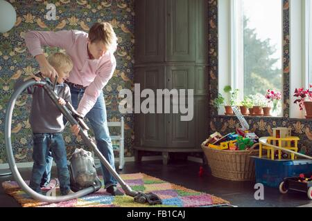 Father and son vacuuming together in living - Stock Image