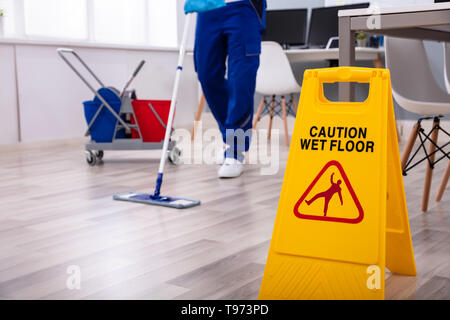 Male janitor with mop cleaning modern office floor - Stock Image