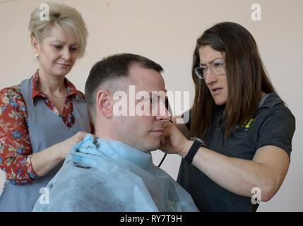 International Space Station Expedition 59 crew member Nick Hague of NASA has his hair cut by a stylist as fellow crew member, Christina Koch of NASA, right, assists at the Baikonur Cosmodrome March 12, 2019 in Baikonur, Kazakhstan. Expedition 59 crew: Christina Koch of NASA, Alexey Ovchinin of Roscosmos, and Nick Hague of NASA will launch March 14th onboard the Soyuz MS-12 spacecraft for a six-and-a-half month mission on the International Space Station. - Stock Image