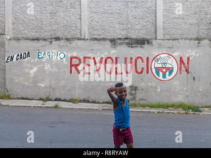 Sweet little Cuban boy giving the thumbs up in front of a sign saying Revolucion in Havana Cuba - Stock Image