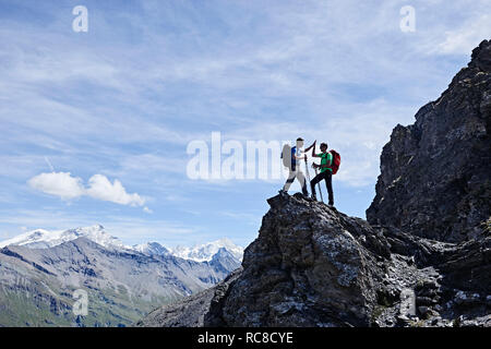 Hikers high fiving on peak of rock, Mont Cervin, Matterhorn, Valais, Switzerland - Stock Image