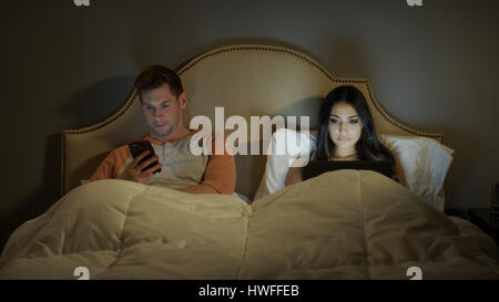 Distracted couple using laptop and cell phone separately in bedroom - Stock Image