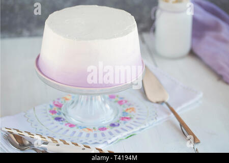Angel cake on a cake stand with cream - Stock Image