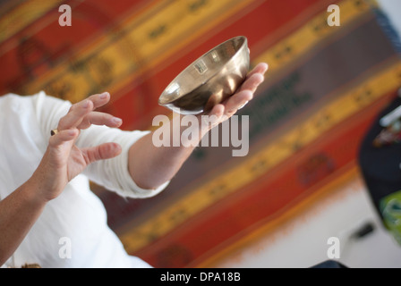 A Tibetan singing bowl in the hands of a therapist - Stock Image