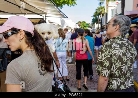 Fort Lauderdale Ft. Florida Las Olas Boulevard Las Olas Art Fair festival man woman dog poodle white pet carry shopping strollin - Stock Image