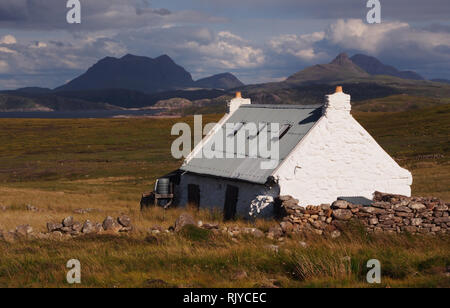 A view of and old crofters home after some renovations, situated away from roads on the Coigach Penninsula, Scotland and mountains in the background - Stock Image