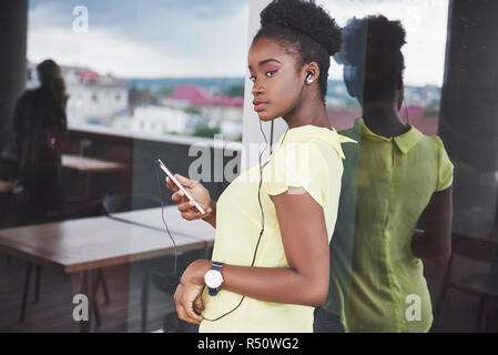Young African American girl with dark curly hair pensive in a cafe. - Stock Image