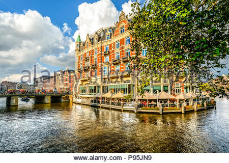 Tourists and local Dutch enjoy an early autumn afternoon as they dine at a waterside cafe and ride their bikes across a bridge over a canal in Amsterd - Stock Image