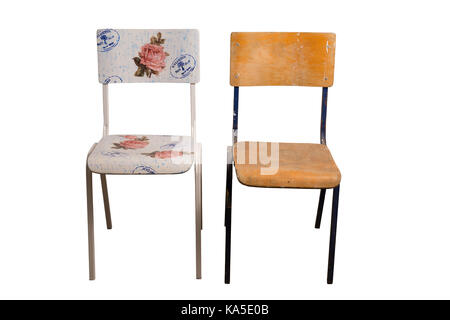 Old school chair decorated with decoupage technique and an old shabby classroom chair that is not yet decorated. - Stock Image