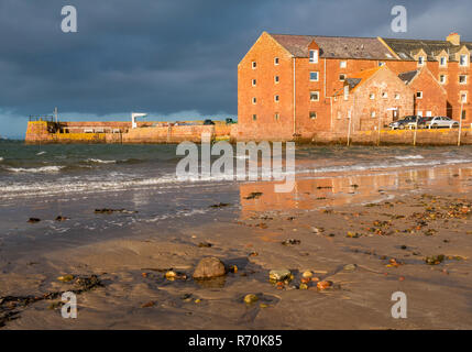 North Berwick, East Lothian, Scotland, United Kingdom. 7th December 2018. UK Weather: A bright sunny but very windy day in the seaside town with gusts of wind of up to 50-60mph forecast Sunshine glistens on the sandy beach at West Bay and lights up the harbour buildings - Stock Image