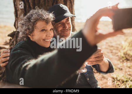 Happy senior couple taking their self portrait with their cell phone on camping day. Man and woman sitting together - Stock Image