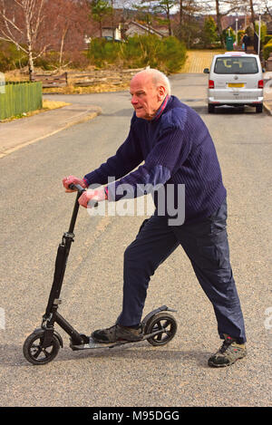87 year old takes to the road on a scooter. - Stock Image