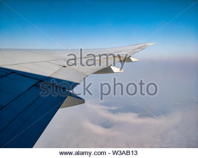 Plane wing above the clouds view cloudy sky - Stock Image