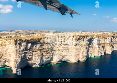 Gozo island from above, under the wing of a small plane. Aerial view of Gozo, Malta. The Rotunda of Xewkija or Casal Xeuchia is the largest in Gozo is - Stock Image