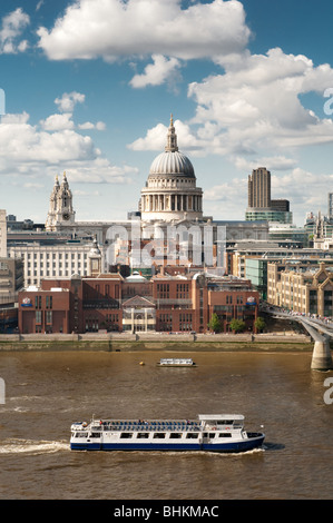 image of guided tour boat on river thames sailing past st pauls cathedral - Stock Image