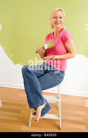 Portrait of smiling adult woman sitting in front of half painted wall with paintbrush - Stock Image
