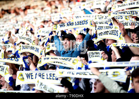 Leeds United fans hold up scarves during the Sky Bet Championship Play-Off, Semi Final, Second Leg match at Elland Road, Leeds. - Stock Image