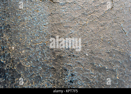 Aged cracked black bitumen tar surface with blue highlights. Copy space area for construction repair ideas and designs - Stock Image