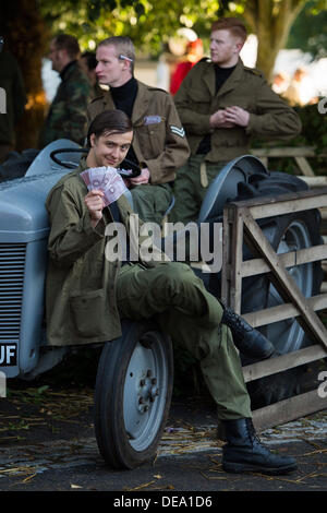 Chichester, West Sussex, UK. 14th Sep, 2013. Goodwood Revival. Goodwood Racing Circuit, West Sussex - Saturday 14th September. Actors dressed in army uniform re-enacting the great train robbery show handful of notes whilst sitting on a grey tractor. Credit:  MeonStock/Alamy Live News - Stock Image