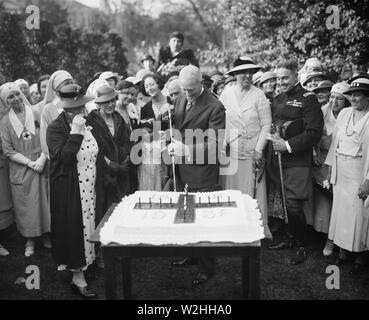 Man cutting large cake ca. 1934 (possibly celebrating the red cross) - Stock Image