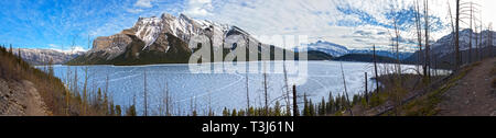 Wide Panoramic Landscape of Frozen Lake Minnewanka and Snowcapped Mountain Peaks in Early Springtime in Canadian Rockies - Stock Image