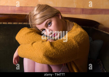 Beautiful young blonde woman in rustic knit sweater sitting on vintage old couch - Stock Image