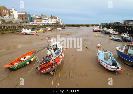 Various small boats lying on the sand in Bridlington harbour at low tide. Bridlington, East Yorkshire. January. - Stock Image