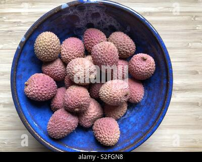 Lychees in a blue ceramic bowl - Stock Image
