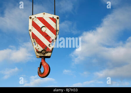 Close up detail of a heavy duty crane load block against a blue sky - Stock Image