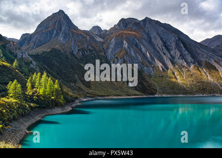 amazing colors of water on the lake Morasco with the shadow of the plants reflected and mountains in background in autumn season - Stock Image
