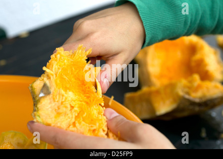 A detail of a person cutting a pumpkin. - Stock Image