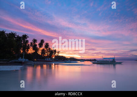 Sunset view of the Dolho Beach with traditional bangka boats, Panglao, Bohol, Philippines - Stock Image