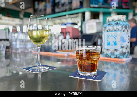 Mixed drink possibly a Bourbon and Coke or Rum and Coke along with a glass of white wine on the bar at Bud and Alley's, Seaside Florida USA. - Stock Image