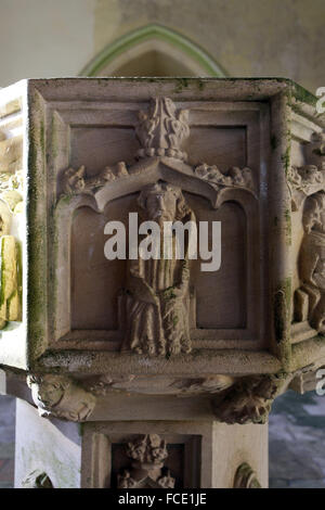 Detail from the 15th century stone font with carvings of the apostles, possibly St Bartholomew with fuller's - Stock Image