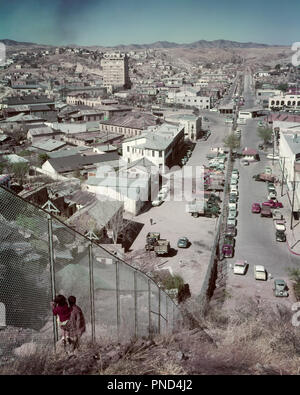 1950s INTERNATIONAL BORDER UNITED STATES AND MEXICO CHAIN LINK FENCE DIVIDES NOGALES AZ & HEROICA NOGALES  - kr2966 HAR001 HARS RISK FATHERS NORTH AMERICA MEXICO HIGH ANGLE ADVENTURE AND CHOICE DADS POLITICS CONCEPTUAL IMMIGRATION FENCES JUVENILES LINK TOGETHERNESS AZ BORDER HAR001 INTERNATIONAL OLD FASHIONED - Stock Image