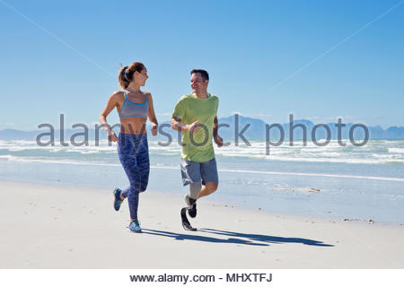 Man Wearing Prosthetic Blade Running Along Shoreline Of Beach With Female Partner - Stock Image