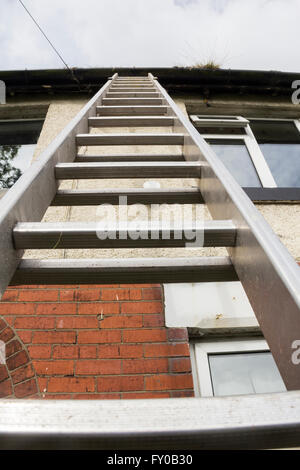 Empty ladder leaning on  the front of a 1930s semi-detached house in Lancashire, UK. The upper floor exterior is - Stock Image